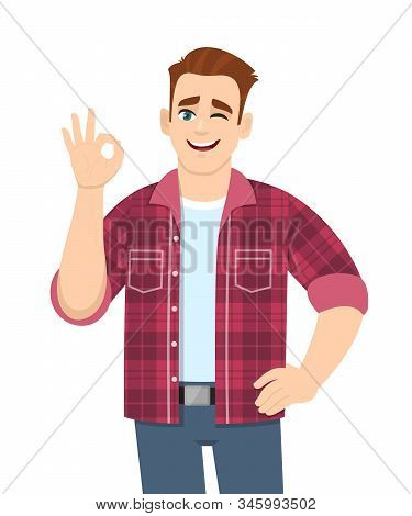 Trendy Young Man Showing Okay Sign And Winking Eye. Stylish Person Making Ok Or Cool Gesture With Fi