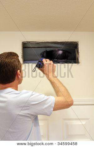 Homem olhando no duto de ar