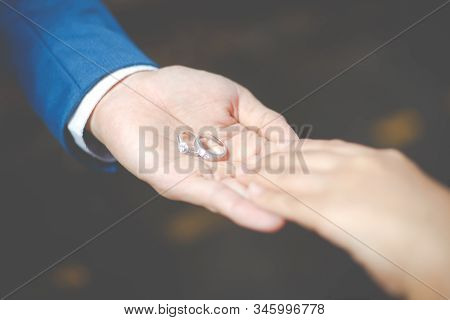 Close-up The Groom Holding Wedding Rings On The Palm And Caressing Hands Of Newlyweds. Gentle Touch