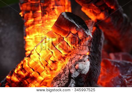 Close-up Of Bright Flashes Of Fiery Flames. Burning Hot Coals And Wood In The Night. Red Burned By H
