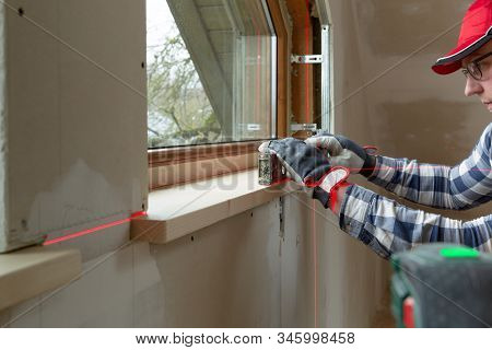Home Improvement Handyman Installing Window Sill In New Build Attic By Using Leveler And Laser Level