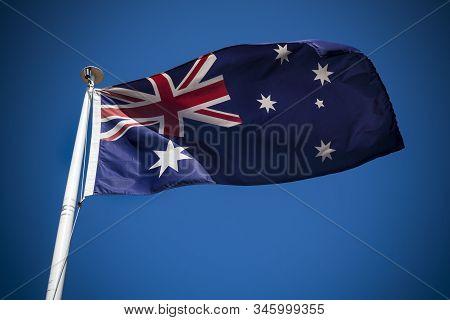 Australia Flag Flying In The Breeze Against Blue Sky
