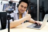 Young asian male gamer casting and broadcasting his online playing video game using smart mobile phone to recording live vlog video. Online influcencer and vlog on social media concept. poster