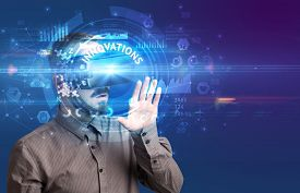 Businessman looking through Virtual Reality glasses with INNOVATIONS inscription, innovative technology concept