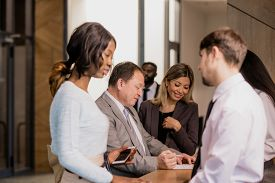 Group of contemporary businesspeople of various ethnicities and ages communicating by reception counter in hotel