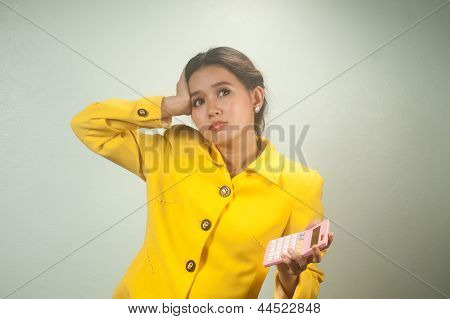 Pretty Young Asian Woman In Yellow Suit Use Calculator.