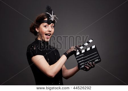 Attractive young woman using clapboard