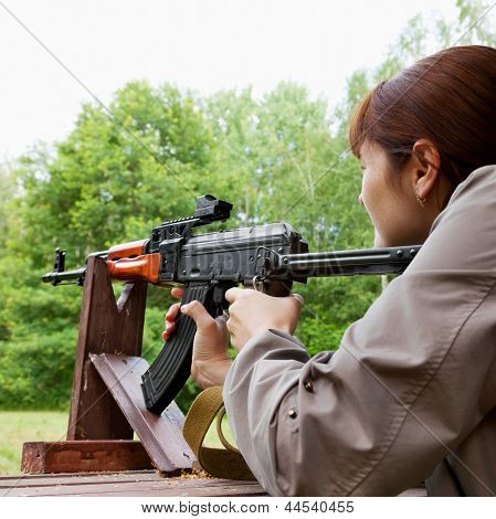 Young Woman Shooting An Automatic Rifle For Strikeball