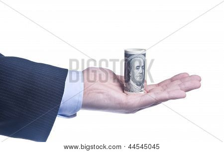 Man's Hand With A Roll Of Dollars