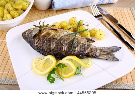 Grilled Fish With Potatoes, Sauce, Lemon And Cutlery