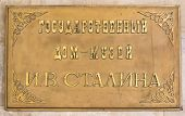 """the sign on the house where Josef Stalin was born in gori Georgia. the translation of the text is """"National home-museum Y.V STALIN"""" poster"""