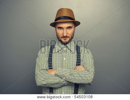 portrait of serious hipster man in straw hat and checked shirt over grey background