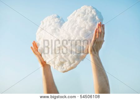 Young man get the heart - cloud to make proffer to his girlfriend from blue clear sky