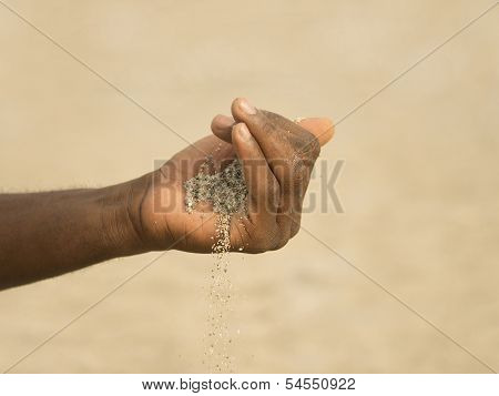 Desertification in the Sahel - African man holding some sand in the hand