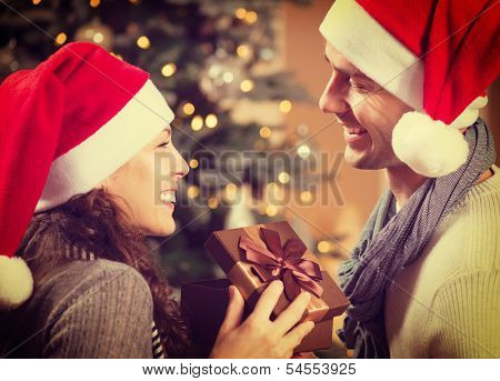 Christmas Gift. Happy Couple in Santa's Hat with Christmas and New Year Gift at Home. Smiling Family Together. Christmas tree