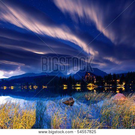 Milky Way over the lake in National Park High Tatra. Dramatic overcast sky. Strbske pleso, Slovakia, Europe. Beauty world.