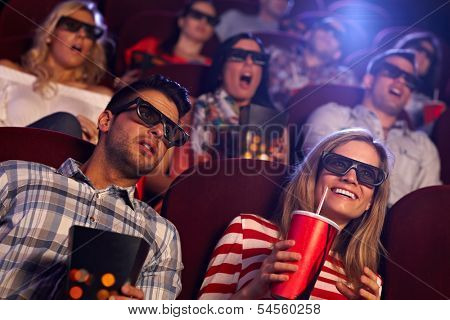 Young people sitting at cinema, watching 3D film, smiling.