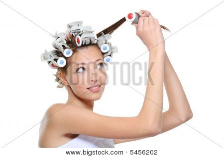 Curling Of Hair By The Young Beautiful Woman