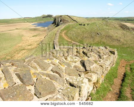 view looking east on the world heritage site of hadrian's wall, northumberland with crag lough in the distance beside the hadrian's wall trail. poster