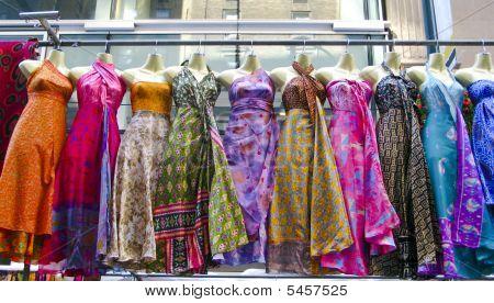 Several Dresses Hanging Up At A Market