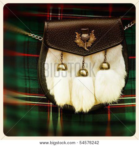 Traditional Scottish sporran over tartan background. Retro style photo.