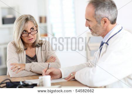 Doctor giving medicine to senior woman for arthritis pain