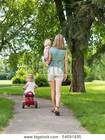 Full length rear view of mid adult woman with children strolling in park poster