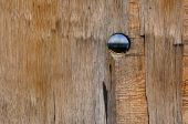 Round hole in a old obsolete wooden door. poster