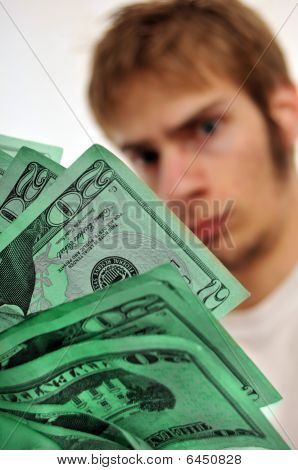 Man Looking At A Wad Of Green Cash
