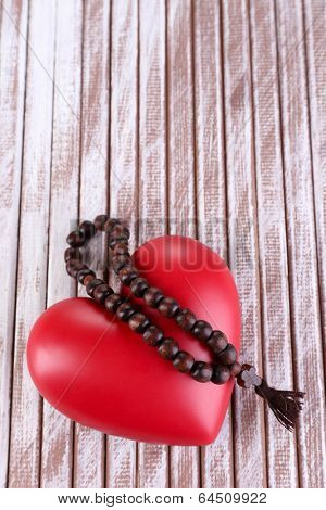 Heart with rosary beads on wooden background poster
