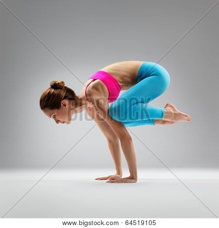 young beautiful yoga posing on a gray studio background