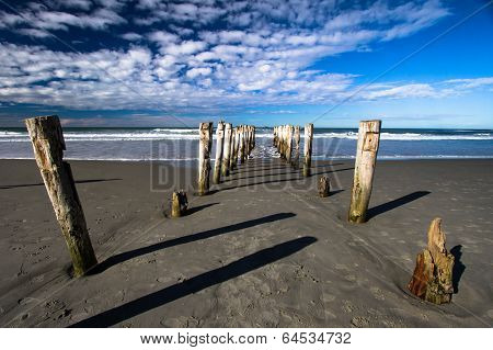 Broken wharf piles in sand leading out to sea
