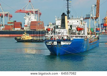 Tugboat assisting bulk cargo ship to harbor quayside poster