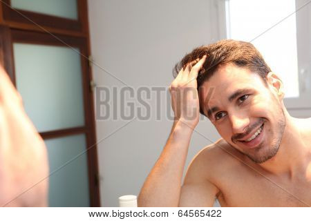 Young man looking at hair in mirror
