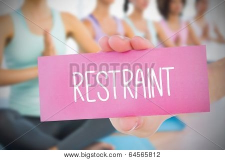 Woman holding pink card saying restraint against fitness class in gym