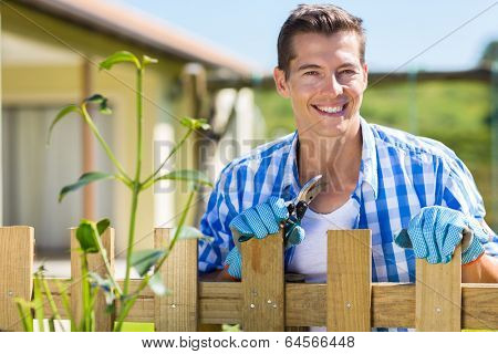 good looking young man standing by home garden fence with pruner