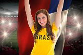 Pretty football fan in brasil t-shirt holding chile flag against vast football stadium with fans in red poster