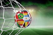 Football in multi national colours at back of net against football pitch under green sky and spotlights poster