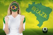 Excited brasil fan in face paint cheering against football pitch with brazil outline and text poster