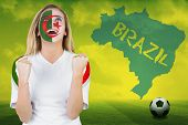 Excited iran fan in face paint cheering against football pitch with brazil outline and text poster