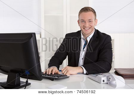Portrait: Handsome young businessman in suit sitting smiling in his office.