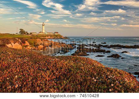 The ocean coast, rocks and lighthouse on sunset.