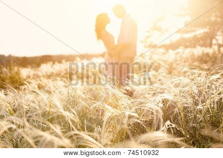 couple kiss at sunset, focus on foreground