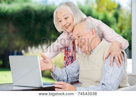 Cheerful senior couple using laptop at nursing home porch