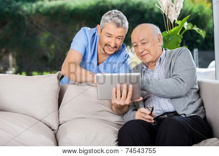 Male caretaker and senior man using tablet PC at nursing home porch