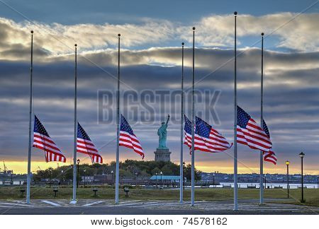 Flags at half staff in front of the Statue of Liberty