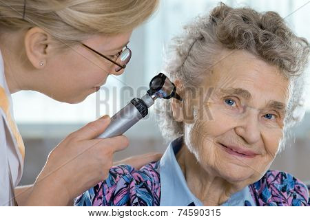 Doctor performing ear exam with otoscope on a  senior patient