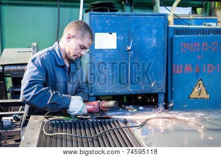 Young worker grinding door