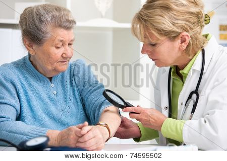 Female doctor examining a mole in the patient