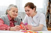 Elder care nurse playing jigsaw puzzle with senior woman in nursing home poster